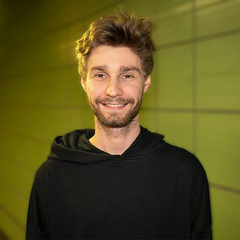 Rene Schepanski mit einem grünem Hintergrund.