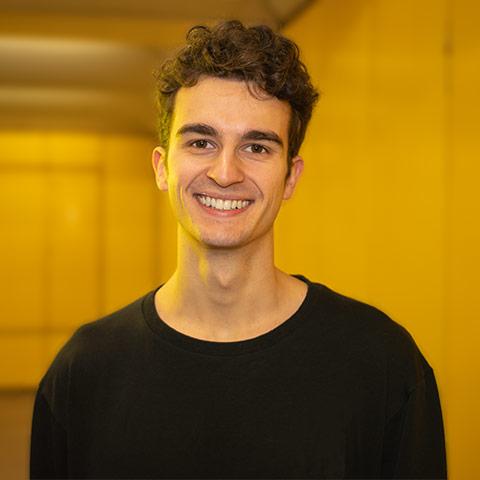 Valentin Huwer, lachend, mit einem gelben Hintergrund.