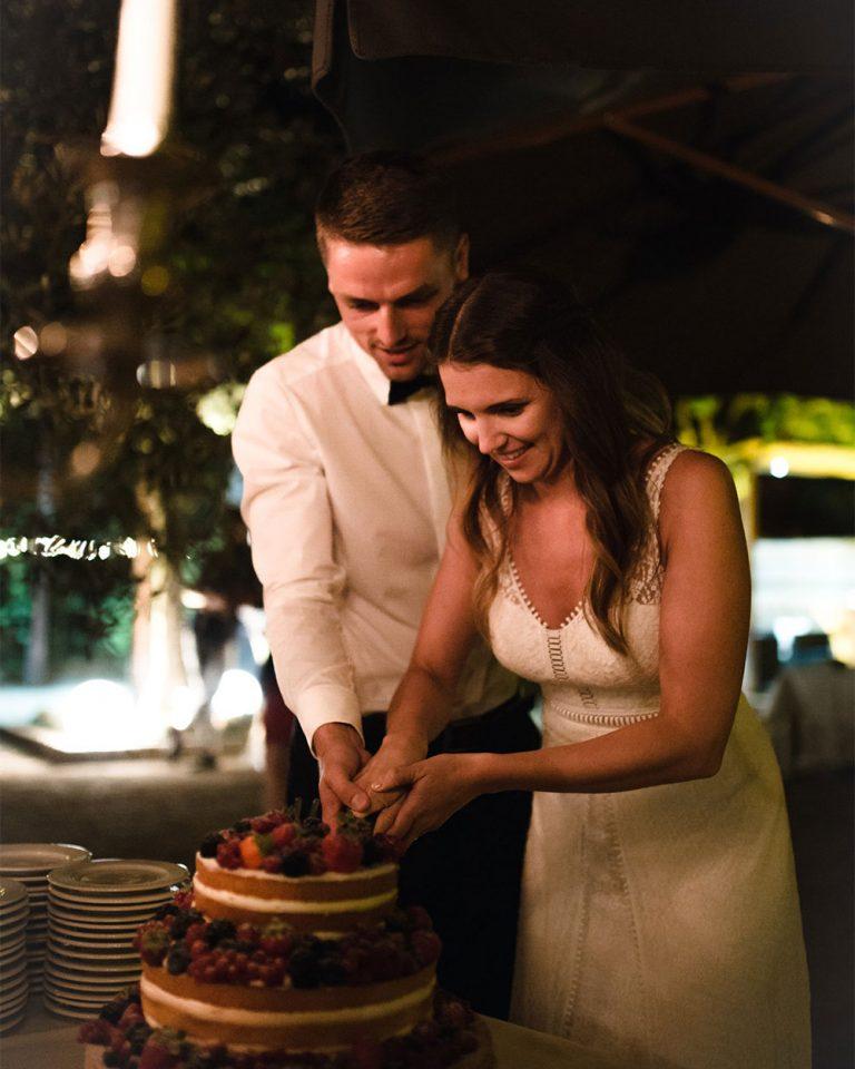Ein paar schneite einen Kuchen an auf einer Hochzeit