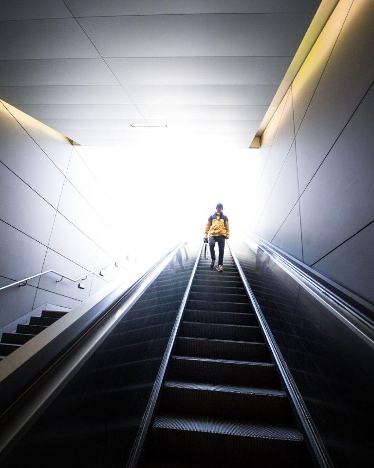 Mann geht rolltreppe runter