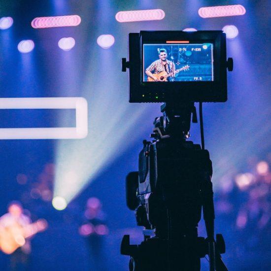 Ausschnitt aus einem Eventvideo, auf dem eine Person auf der Bühne Gitarre spielt.