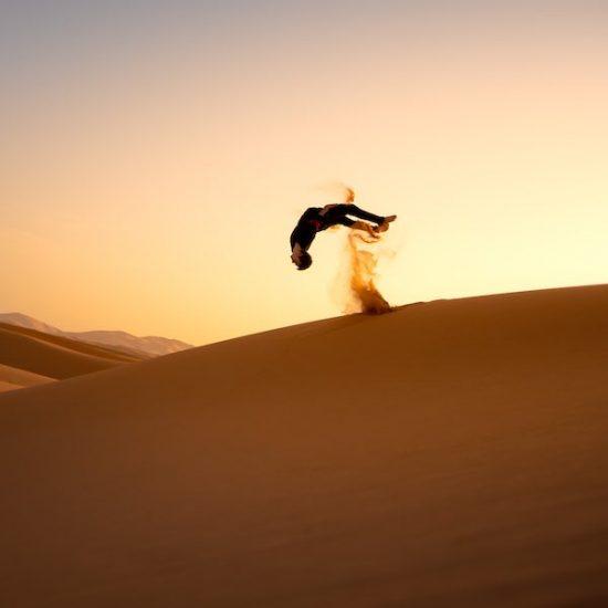Person macht backflip in der Wüste