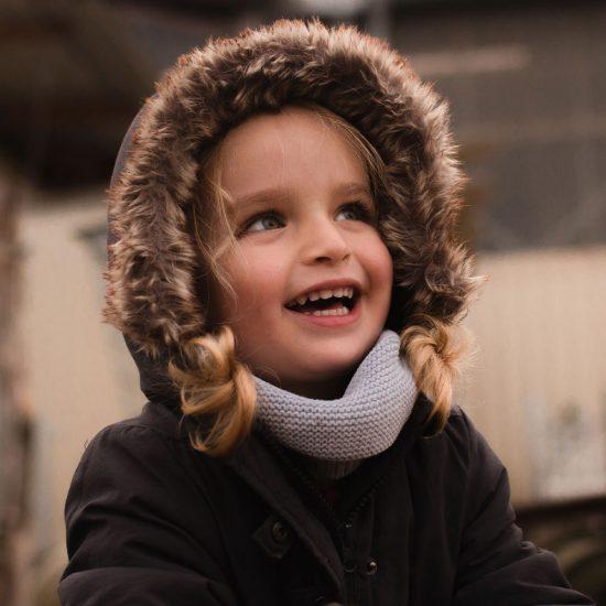 Lachendes kleines Mädchen mit einer Fell Mütze auf