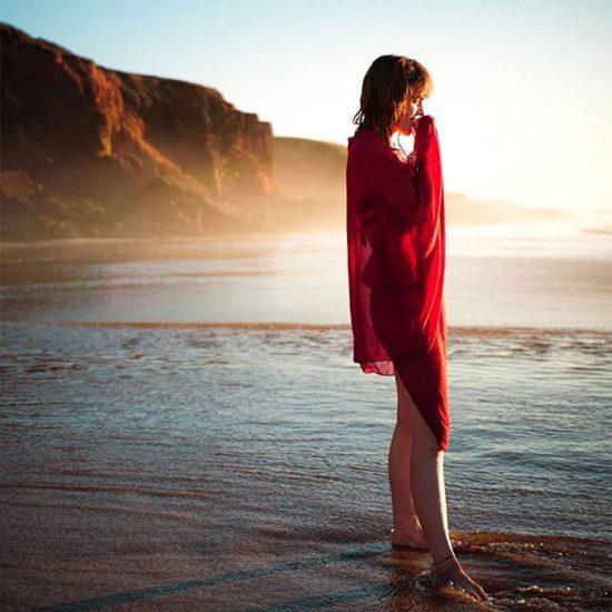 Frau steht am Strand im Wasser